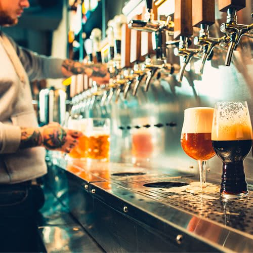 beer taps filling up different types of beer glasses