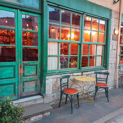 outside entrance of quaint bar with patio furniture